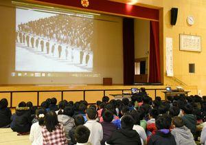 記録映画の上映では、五十数年前の運動場での全校集会の人数の多さに子どもたちから驚きの声が上がった=武雄市の武雄小