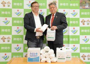 神埼市にマスクと除菌液などを寄贈した大串製菓の大串久昭代表(左)と松本茂幸神埼市長=神埼市役所