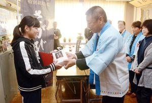 須古小の代表として贈呈式に出席した吉岡真美さん(左)に特別栽培米のさがびよりを手渡すJAさが白石地区特別栽培米部会の小野正博部会長=白石町の須古小