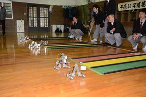 手作りした尺取り虫型ロボットの速さを競った大会=有田町の有田工高