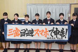 揮毫した確定申告の広報用作品を掲げる神埼高書道部の部員たち=神埼市の同校