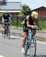 沿道の声援を受けながら自転車で疾走する選手たち=佐賀市東与賀町