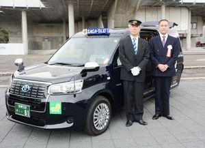 乗降しやすい設計の新型車両を導入した佐賀タクシーの牛島秀図社長(右)=佐賀市の県立博物館前