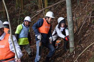 山の斜面に生えた竹を伐採する参加者=基山町園部