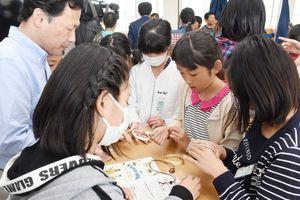 石でできたブレスレットを触る児童たち=佐賀市巨勢町の巨勢小学校