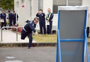 パネルを犯人と想定して、カラーボールを模した水風船を走りながら投げる練習をする参加者=嬉野市の長崎道嬉野料金所