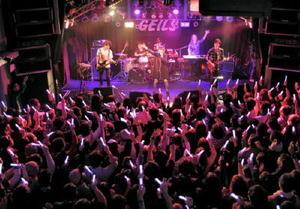 「モットアタシヲ」の曲に合わせ手を振り、ライブを盛り上げるカノエラナさん(中央奥)=佐賀市のガイルス