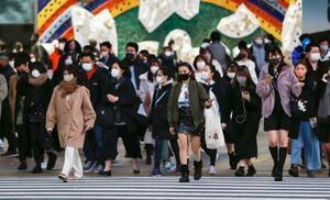 東京・渋谷のスクランブル交差点を歩くマスク姿の人たち。国内で初めて新型コロナウイルスの感染者が確認されてから1年を迎えた=15日午後