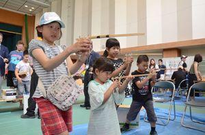 竹製のゴム鉄砲を構え、的を狙う子どもたち