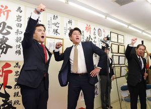 事務所開きで支持者とともに気勢を上げる岩田和親氏(左)=佐賀市水ケ江
