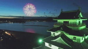 【上空から】ライトアップされた唐津城天守閣越しに見える打ち上げ花火=小型無人機ドローンで撮影