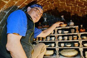 納得のいかない器を二度焼きするため、窯に作品を詰める岡本作礼さん=唐津市厳木町の作礼窯