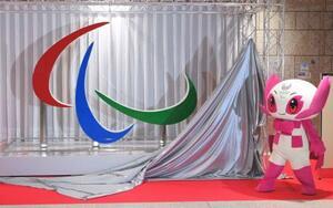 東京パラリンピックの開催まで100日となり除幕されたシンボルマーク「スリーアギトス」のモニュメント。右は大会マスコットの「ソメイティ」=16日午後、都庁(代表撮影)