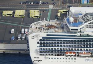 クルーズ船「ダイヤモンド・プリンセス」付近に待機するバス(左上)=19日午前10時40分、横浜港(共同通信社ヘリから)