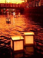 ちょうちんの明かりに照らされた多布施川をゆったりと流れる灯籠=15日午後8時ごろ、佐賀市の護国神社(撮影・山田宏一郎)