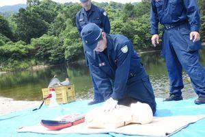 AEDを使用した心肺蘇生法を行う警察官=神埼市神埼町尾崎の天神尾池