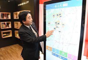 デジタルサイネージを操作する松田一也町長=JR基山駅