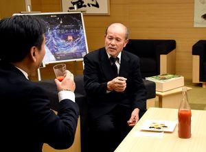 生産しているトマトジュースを紹介しながら山口祥義知事(左)へ受章を報告する水田強さん=佐賀県庁
