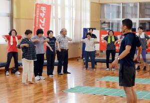介護予防の一環で開かれた筋力アップ教室で体を動かす住民たち=神埼市の市中央公園体育館