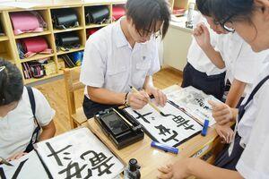 児童に当てはめてもらった漢字で、自分の名前を書くアンドリュー・スパララゲンさん=佐賀市の金立小
