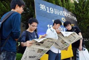 「新聞週間」に合わせたPR活動で、配布された新聞を読み進める学生たち=佐賀市の佐賀大学本庄キャンパス