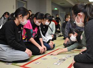 伊万里観光いろはかるた小学校交流大会で札を奪い合う児童=伊万里市の市民センター