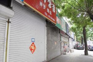北朝鮮向けの商品を扱う商店が並ぶ中国遼寧省丹東市の通り。シャッターを下ろした店が目立つ=7日(共同)