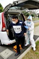 防護服に身を包んだ鳥栖市保健福祉事務所所員(右)が、新型インフルエンザの模擬患者を病院に搬送する手順を確認した訓練=みやき町の東佐賀病院