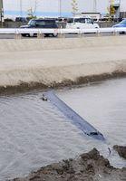 陸自ヘリ墜落事故で、交通量の多い国道264号沿いの水路に落下したメインローター羽根とみられる残骸=6日午後2時40分、神埼市千代田町詫田