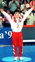 1992年バルセロナ五輪の柔道男子71キロ級で優勝し、表彰式で両手を上げる古賀稔彦(共同)