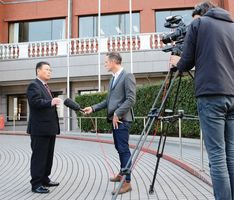 イギリスのニュース番組の取材を受け町の子育て支援施策を紹介する岩島正昭町長(左)