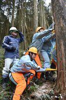 演習林で生徒の伐採作業を見守る伊万里農林高の松本寛教諭(左)=伊万里市の腰岳