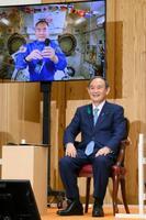 国際宇宙ステーションに長期滞在中の野口聡一飛行士(画面)と笑顔で交信する菅首相=20日夜、首相官邸