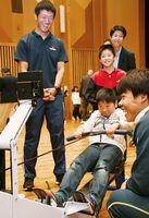 選手に見守られ、トレーニング機器で陸上ボートこぎ体験をする児童=富士公民館