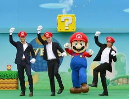 「SUPER NINTENDO WORLD」の着工式で、ポーズをとるマリオと関係者=8日午前、大阪市のUSJ