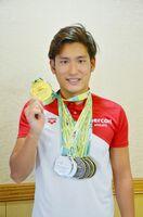 世界ろう者水泳選手権での金メダルを手に笑顔を見せる金持選手=唐津市役所