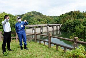 県の担当者からダムの事前放流について説明を受ける峰達郎市長(右)=唐津市神田の平木場ダム