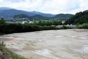 野球グラウンドとして整備中の佐賀競馬場の駐車場跡地。左奥は競馬場の観客スタンド=鳥栖市江島町