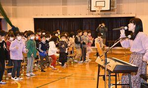 児童と「ウィ・ウィル・ロック・ユー」を歌う古賀さん(右)=佐賀市の開成小