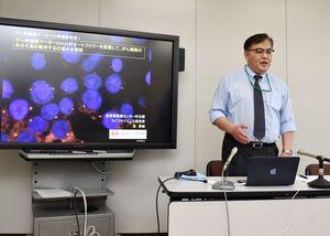 研究で発見したがん幹細胞マーカーの機能について説明する泉秀樹部長=県庁
