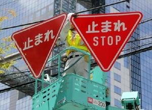 英語併記の新デザイン(右)に交換される「止まれ」の道路標識=1日午前、大阪市