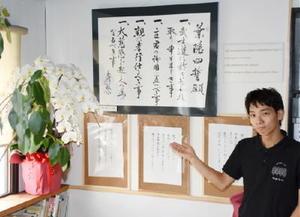 ゲストハウスに飾られている「葉隠四誓願」と店長の髙瀬さん=佐賀市神野東