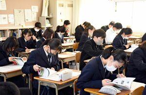 唐津検定の公式本「唐津探訪」を開きながら模擬試験に臨む唐津西高の生徒たち=唐津市の同校