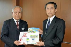 クリアファイルを受け取った杉﨑士郎会長(左)と久米章也副会長=佐賀県庁
