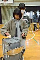候補者の名前を書き、一票を投じる児童ら=佐賀市の西与賀小体育館