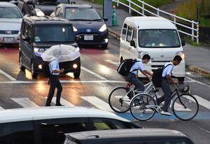 小雨の中、横断歩道を渡る人たち=8日午後7時ごろ、佐賀市本庄町