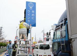 早めのウインカー(合図)を呼び掛ける看板を設置する作業員=佐賀市の佐賀北警察署前