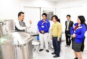 化粧品原料をつくる装置の前で、見学者に説明するクレコスの暮部達夫社長(左)=唐津市石志