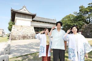 佐賀城鯱の門で「2(ピース)」のポーズで記念撮影する小栗旬さん(中央)=佐賀市の佐賀城(提供)