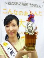「ハブ入りハブ酒」を手にする琉球新報社の名嘉真智美さん=28日午後、福岡市
